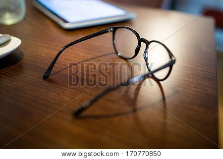 Close-up of spectacle and mobile phone on wooden table in restaurant