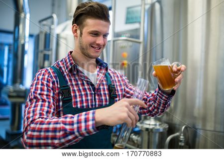 Brewer pouring beer in hydrometer cylinder at brewery factory