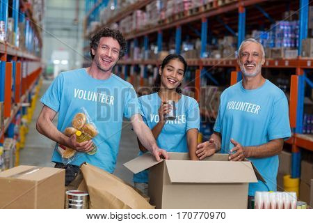 Happy volunteer are posing and smiling during work in a warehouse