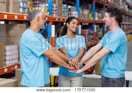 Happy volunteers are joining hands and looking each other in a warehouse