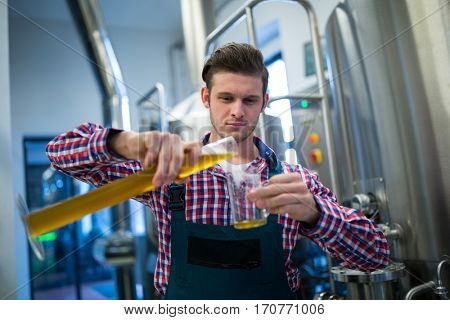 Brewer pouring beer in pint glass at brewery factory