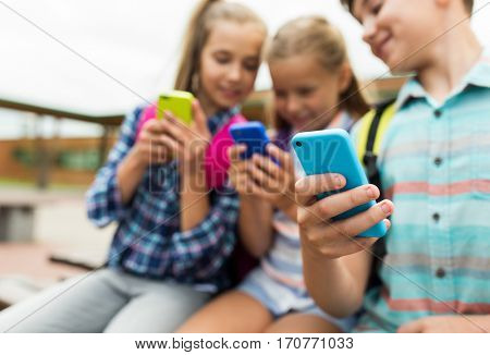 primary education, friendship, childhood, technology and people concept - group of happy elementary school students with smartphones and backpacks outdoors