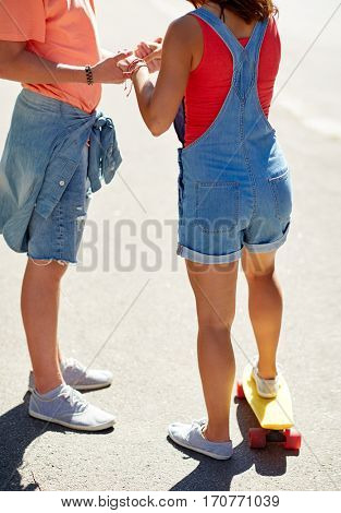 summer, love, extreme sport and people concept - close up of teenage couple riding short modern cruiser skateboard on city street