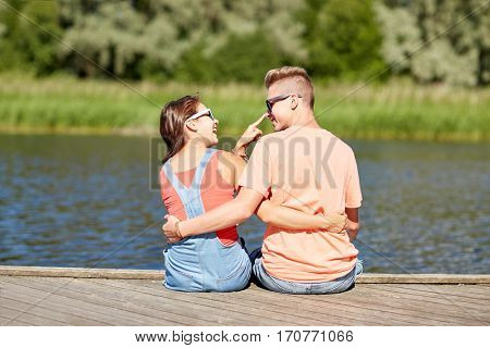 vacation, love and people concept - happy teenage couple sitting and hugging on river berth at summer