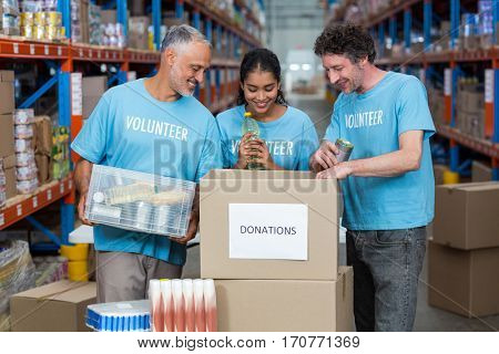 Happy volunteers are looking inside a donations box in a warehouse