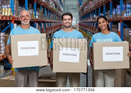 Happy volunteers are holding donations boxes and looking the camera in a warehouse