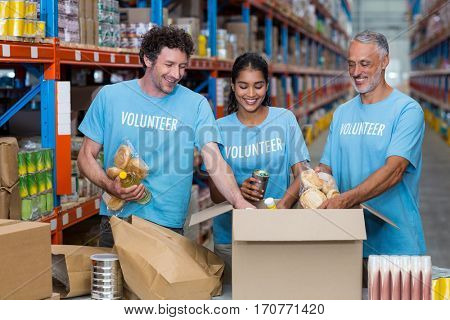 Happy volunteers tidy some goods in cardboard box in a warehouse