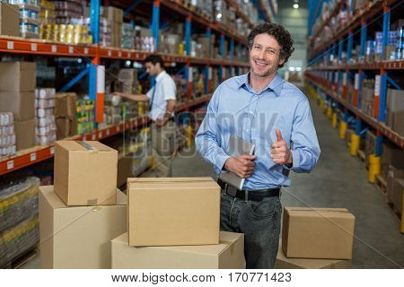 Portrait of happy manager posing in the middle of cardboard boxes with thumbs up in a warehouse