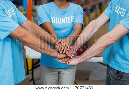 Close up of volunteers joining hands in a warehouse