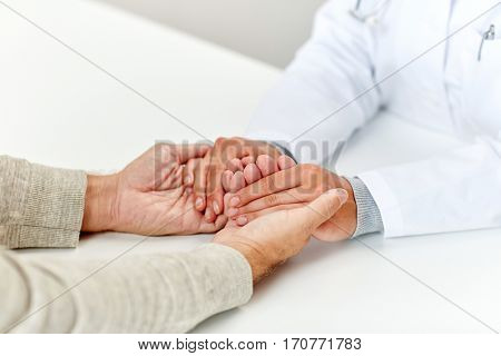 medicine, age, support, healthcare and people concept - close up of doctor or nurse holding senior man hand at hospital