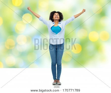 people, success and portrait concept - happy african american young woman with raised fists looking up over summer green lights background