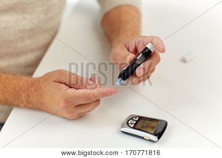 medicine, age, diabetes, healthcare and old people concept - senior man with glucometer checking blood sugar level at home