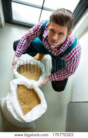 Portrait of brewer with sack of grains at brewery factory
