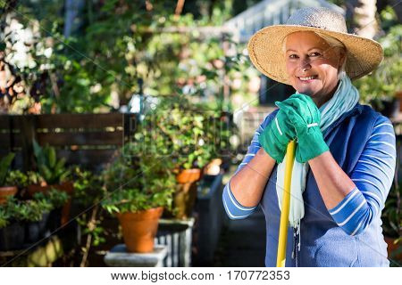 Portrait of happy mature female gardener at botanical garden
