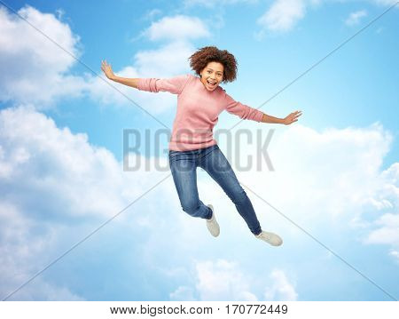 people, motion and action concept - happy african american young woman jumping over blue sky and clouds background