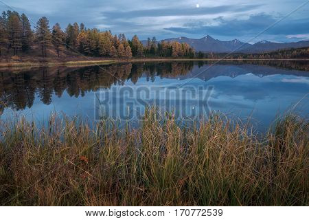 Mirror Surface Lake Autumn Landscape With Mountain Range On Background And Early Evening Moon. Wild Nature Forest Water Scenery Photo With Calm Atmosphere Image.