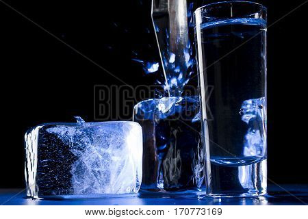 Vodka glass and ice cubes  on black background
