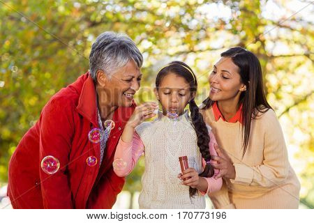 Playful multi-generation family blowing bubbles at park