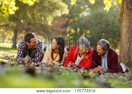 Joyful family lying on front against trees at park