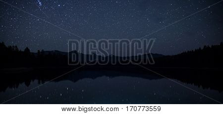 Mirror Surface Lake Breathtaking Landscape With Mountain Range At Night With Sky With Myriads Of Bright Stars. Wild Nature Forest Water Scenery Photo With Calm Atmosphere Image.
