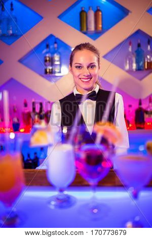 Portrait of young barmaid standing at illuminated bar counter