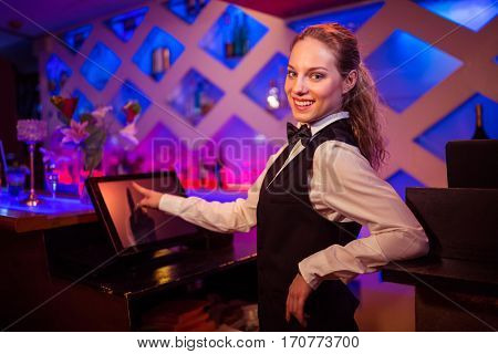 Portrait of beautiful barmaid pointing at modern cash register at bar counter