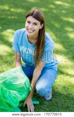 Portrait of volunteer woman collecting rubbish in garden