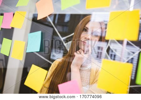 Thoughtful businesswoman looking on sticky notes in creative office