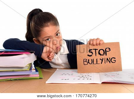 young cute hispanic schoolgirl scared in stress holding paper with text stop bullying written looking desperate asking for help sitting at school desk alone in victim children bullied abuse concept poster