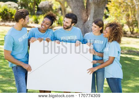 Group of volunteer holding blank sheet in park