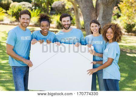 Portrait of volunteer group holding blank sheet in park