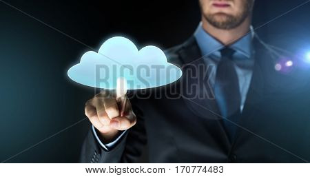 business, people, future technology and cyberspace concept - close up of businessman touching virtual reality screen with cloud computing icon projection over dark background