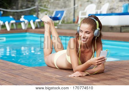 Happy woman with smartphone relaxing near swimming pool listening with earbuds to streaming music. Beautiful girl using her mobile phone