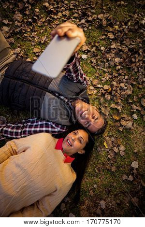 High angle view of couple taking selfie while lying on back at park