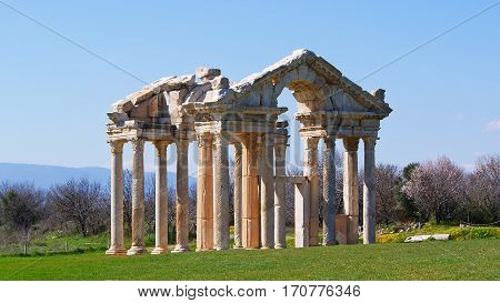 ruins of a Temple of Aphrodite on a green grass field under a blue sky in the Mediterranean region
