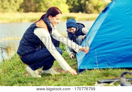 camping, tourism, hike, family and people concept - happy mother and son setting up tent outdoors