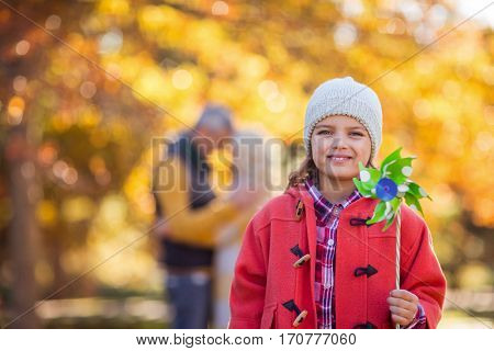 Portrait of smiling girl holding pinwheel toy at park during autumn