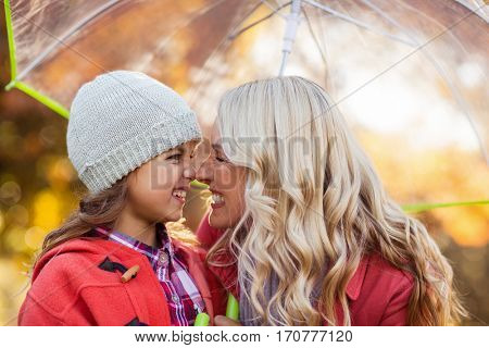 Happy mother and daughter rubbing noses while holding umbrella at park