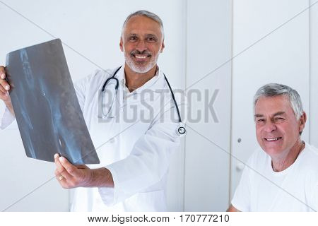 Male doctor discussing x-ray with senior man in hospital
