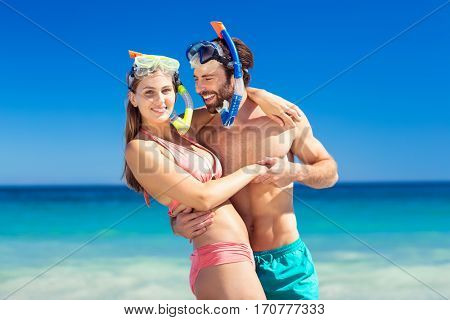 Happy young couple embracing each other on beach