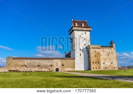 Hermann Castle facade on sunny day, Narva, Estonia. The Herman Tower was founded in 1256 by the Danes who conquered Northern Estonia.