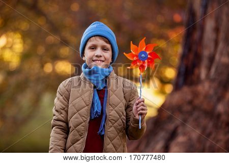 Portrait of smiling boy holding pinwheel while standing at park
