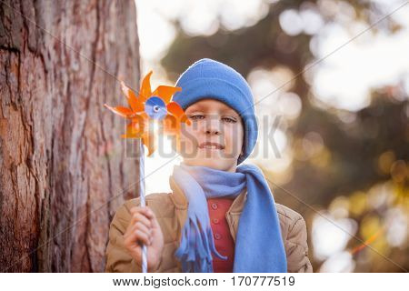 Low angle portrait of smiling boy holding pinwheel while standing at park