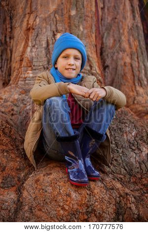 Portrait of smiling boy hugging knees while sitting on tree trunk at park
