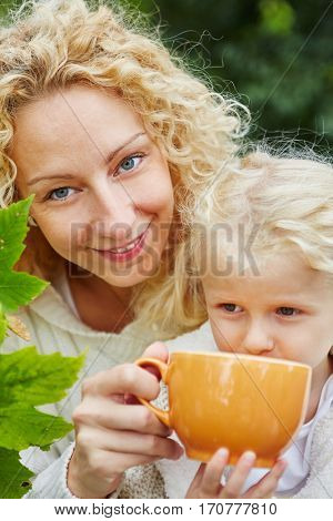 Happy mother and daugther drinking tea together in autumn