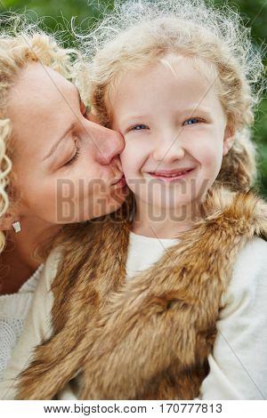 Mother kissing happy daugther with love in autumn
