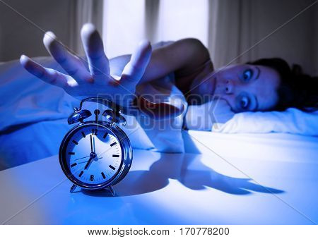 shock upset young woman at home in bed not wanting to wake up turning off her alarm clock with a crazy look on her face and dramatic shadow light in getting up early morning concept