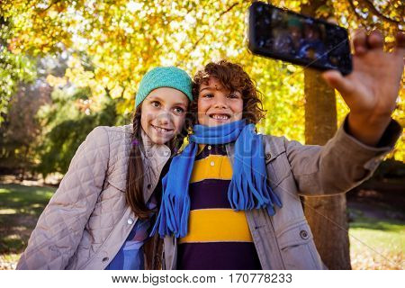 Happy siblings taking selfie while standing at park during autumn