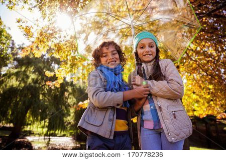 Low angle view of siblings holding umbrella while standing in park