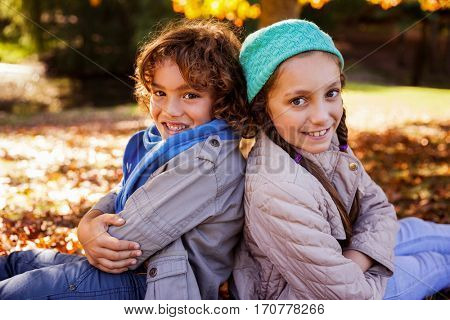 Portrait of smiling siblings with arms crossed while sitting in park during autumn